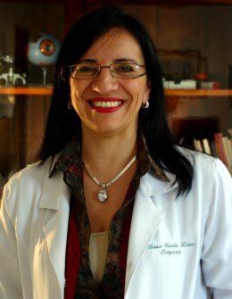Fotografia colorida no formato 3x4 centímetros. Ela é uma mulher de cabelos pretos e lisos, usa óculos, batom vermelho, um colar e veste um jaleco branco. Ela olha em direção à câmera e sorri.