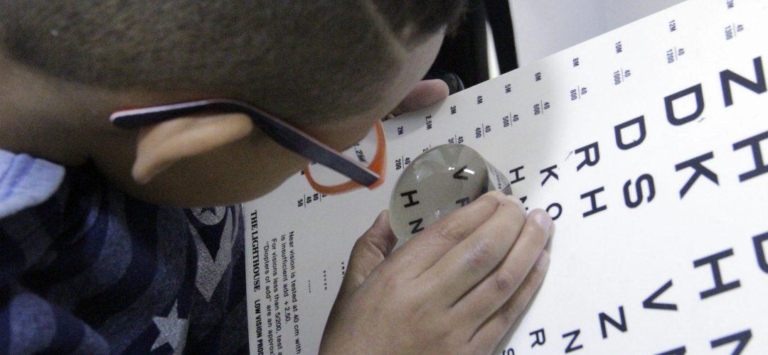 fotografia colorida de menino visto de cima. Ele usa óculos e está manuseando uma lupa de ampliação em uma tabela com letras diversas.