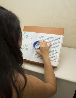 Fotografia colorida de uma mulher de cabelos compridos. Ela está de costas para a imagem, segura uma lupa de ampliação sobre um livro posicionado em uma mesa.
