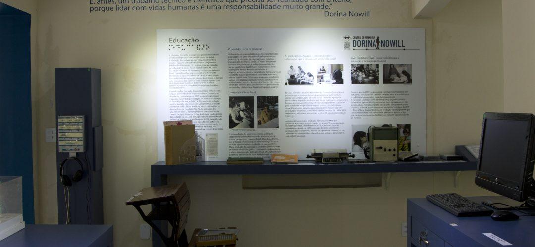 Fotografia colorida de bancada do Centro de Memória Dorina Nowill. Há um painel com textos diversos e uma bancada com vários itens relacionados à acessibilidade.