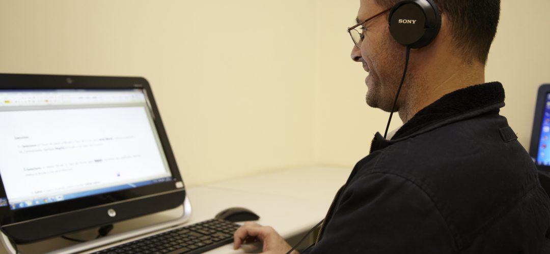 Fotografia colorida de homem sentado em frente a um computador, usa fone de ouvido e sorri.
