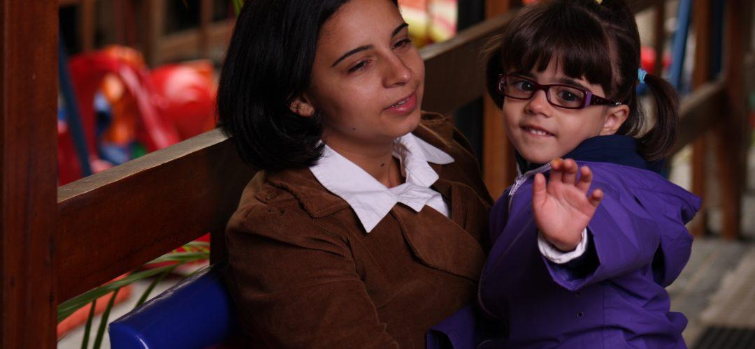 Fotografia colorida de mulher segurando uma menina de cerca de 3 anos no colo. A menina está com a mão esquerda levantada, usa óculos e olha em direção à câmera.