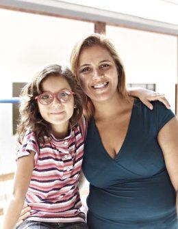 Fotografia colorida de menina de cerca de 7 anos e uma mulher. Elas se abraçam e sorriem para a câmera.