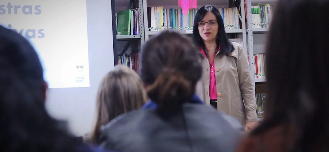 Fotografia colorida de pessoas sentadas de costas que assistem uma mulher palestrar. Ela está de frente para a câmera.