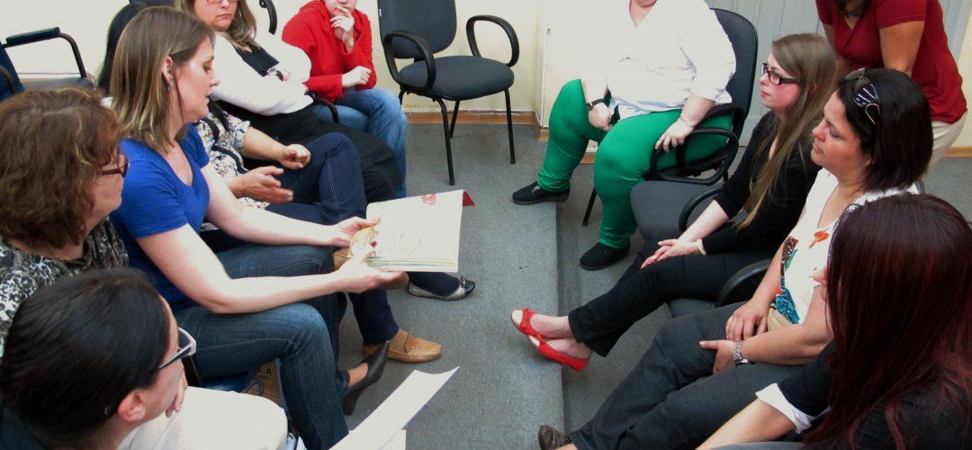 Fotografia colorida de cerca de 8 mulheres estão sentadas em círculo. Uma delas, à esquerda, segura um livro enquanto fala com as demais.