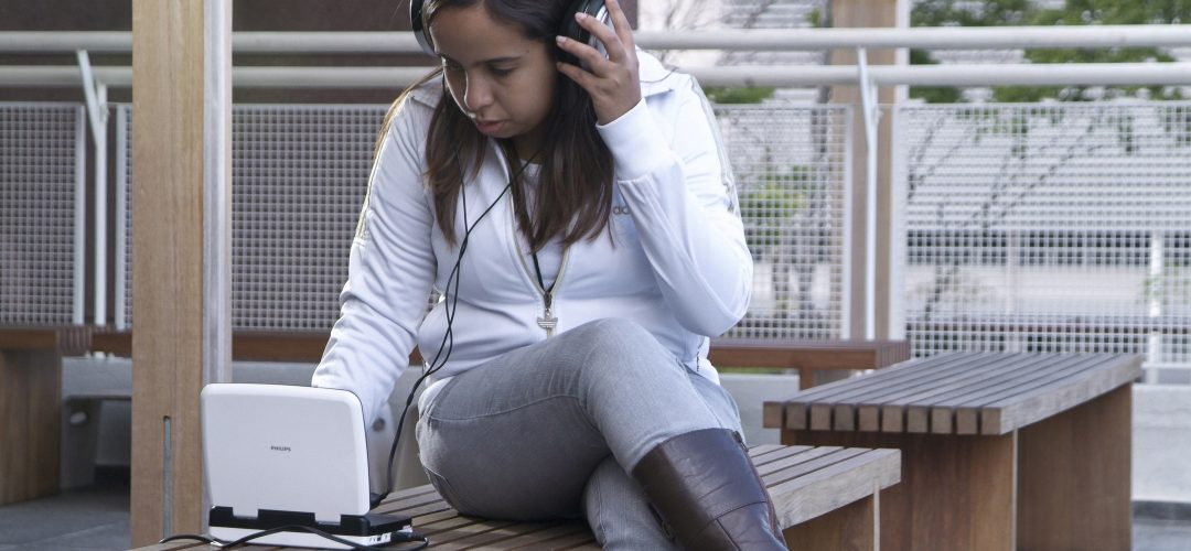 Fotografia colorida de uma moça sentada em um banco de madeira, ela está com fones de ouvido. Com uma mão segura no fone e a outra manuseia um tablet.