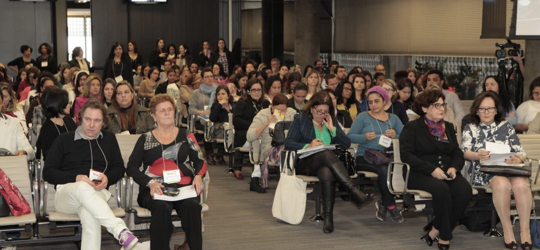 Fotografia colorida de auditório com dezenas de pessoas sentadas.