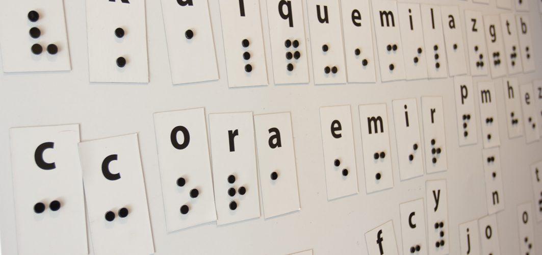 Descrição de imagem: fotografia de um grande painel, com fundo branco, em que há o alfabeto braille, em grande escalam, com as letras espalhadas por ele.