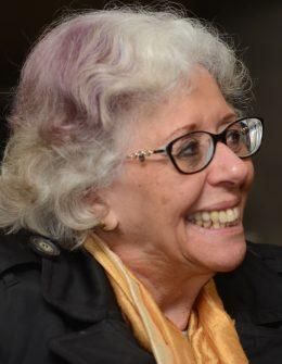 Descrição de imagem: Fotografia colorida de Marta Gil, levemente de perfil e sorrindo. Ela tem cabelos grisalhos e usa óculos.