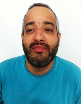 Descrição de imagem: Fotografia colorida de Manoel Negraes em estilo 3x4 cm. Ele tem pele morena clara, cabelos curtos e barba. Veste uma camiseta azul. Fim da descrição.