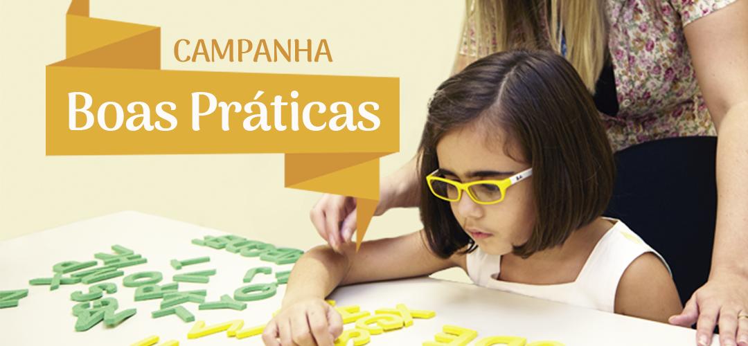 Descrição de imagem: Fotografia colorida de uma menina morena, usando óculos de armação amarela. A menina está manuseando várias letras do alfabeto com o auxílio de uma mulher, que está em pé. Fim da descrição.